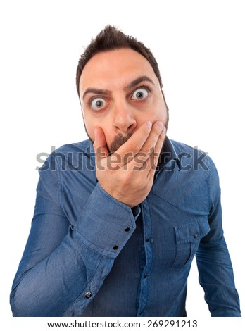 Young man with expression of fright on white background - stock photo