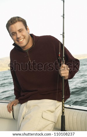 Young man with fishing rod on yacht - stock photo