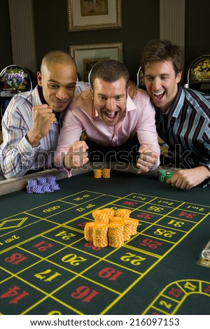 Young man with friends gambling at roulette table in casino, smiling - stock photo