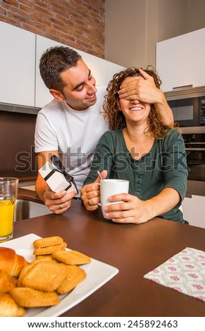 Young man with gift box closing his girlfriend eyes for a surprise while having breakfast on the home kitchen - stock photo