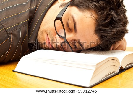 young man with glasses fell asleep during reading - stock photo