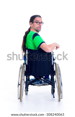 young man with glasses in a wheelchair in front of white background from the back - stock photo