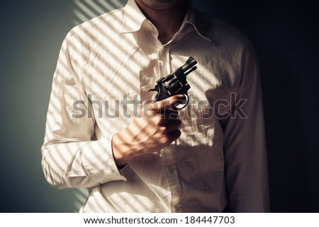 Young man with gun by the window is covered in shadows from the blinds - stock photo