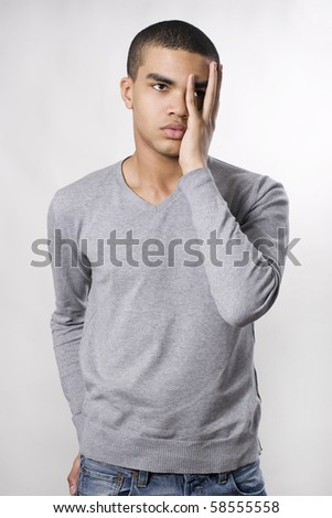 Young man with hand over eyes, looking through fingers - stock photo