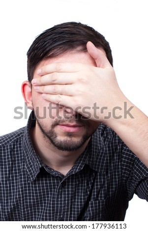 Young man with hand over his eyes isolated on white background - stock photo