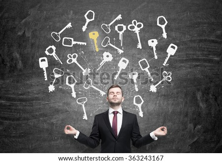 Young man with hands in pose of meditation and eyes closed in search of the right solution which are presented as keys around him. Black background. Concept of finding a solution. - stock photo