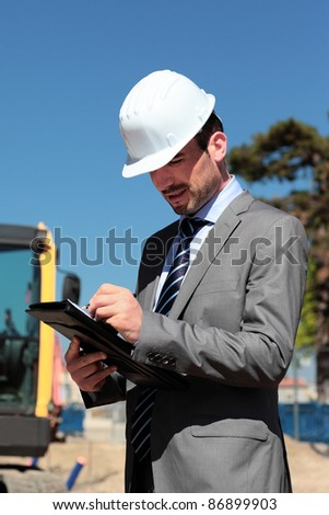young man with hardhat and pen on building site - stock photo