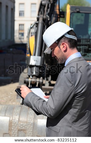 young man with hardhat on building site - stock photo