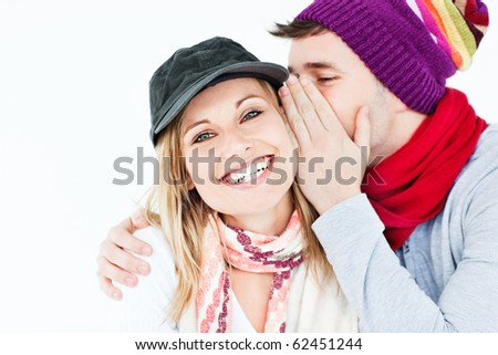 Young man with hat whispering something to his female friend against a white background - stock photo