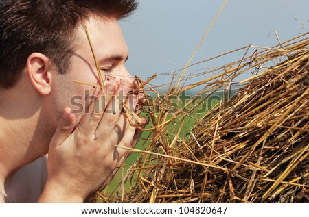 Young man with hay portrait. - stock photo