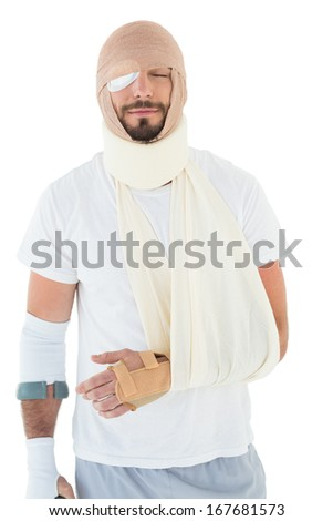 Young man with head tied up in bandage and broken hand over  white background - stock photo