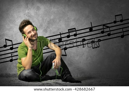 Young man with headphones listening to music sitting on grey wall background - stock photo