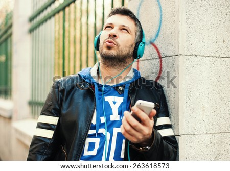 Young man with headphones playing with smart phone - stock photo