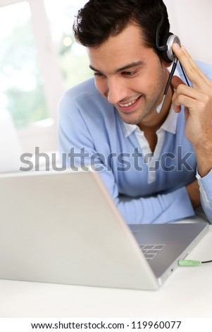 Young man with headset chating through webcamera - stock photo