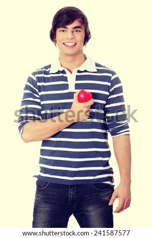 Young man with heart shaped toy - stock photo