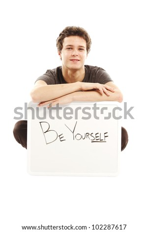 Young man with hip style holding sign that says be yourself - stock photo