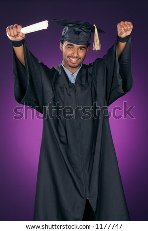 young man with his arms raised is celebrating his achievement as he graduate's - stock photo