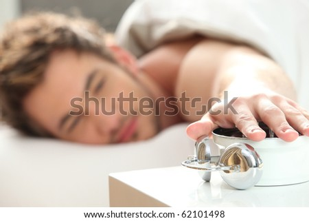Young man with his hand on an alarm clock - stock photo
