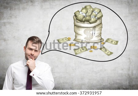 young man with his hand to the chin thinking about money. A picture of a bag of money to the right. Front view. Concrete background. Concept of having a lot of money. - stock photo