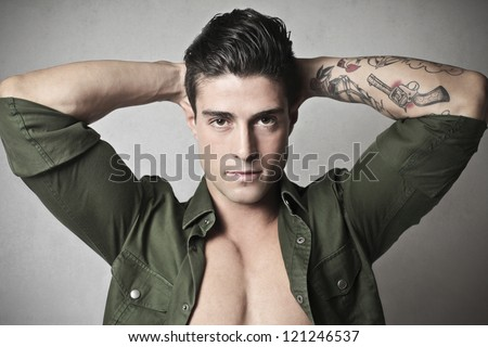 Young man, with his hands behind his head, showing the tattoo on his left forearm - stock photo