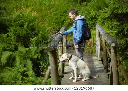 Young man with his labrador on trip. - stock photo