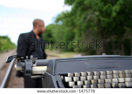 Young man with his typewriter on the train tracks. - stock photo