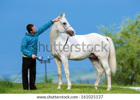 Young man with horse - handsome - stock photo