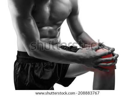 Young man with knee pain,isolated on white background, monochrome photo - stock photo