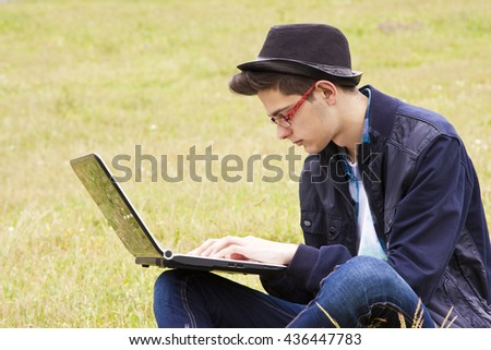 young man with laptop outdoors - stock photo