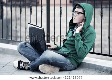 Young man with laptop sitting on the sidewalk - stock photo