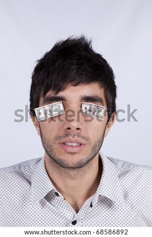 Young man with little dollar bills covering his eyes - stock photo