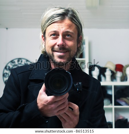 Young man with long blond hair holding photo camera - stock photo