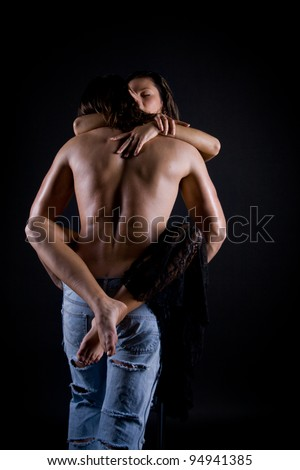 young man with long hair and a muscular back passionately engaged in sex with a beautiful girl at the wall - stock photo