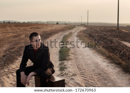 young man with luggage on a road - stock photo