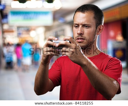 young man with mobile phone at shopping center - stock photo