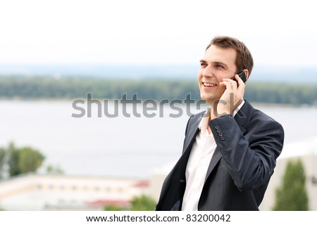 young man with mobile phone outdoors - stock photo