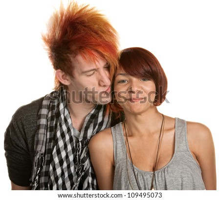 Young man with mohawk kisses mixed girlfriend over white - stock photo