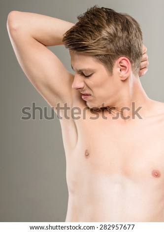 Young man with naked torso smells his armpits on grey background. - stock photo
