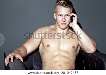 Young man with naked torso using his mobile phone - stock photo