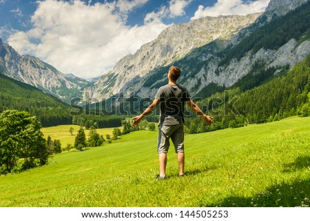 Young man with open arms charging energy from a nature. - stock photo