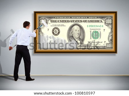 Young man with paint brush and banknote painted on the wall - stock photo