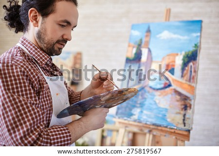 Young man with palette and paintbrush working in studio - stock photo