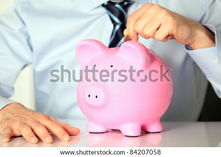 young man with pink piggy bank and coin - stock photo