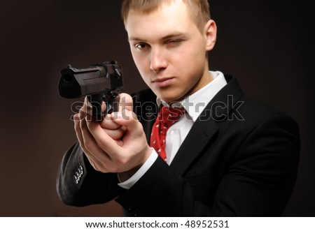 Young man with pistol over dark background. Focused on pistol. - stock photo