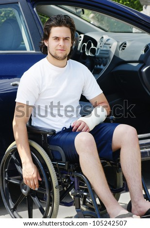 Young man with plaster cast after an accident in wheelchair arriving or leaving the hospital, car with opened door in the background. - stock photo