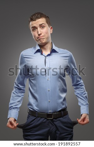 Young man with pockets turned inside out. Concept - no money, crisis, problems - stock photo