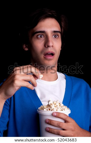young man, with popcorn watching, on black background. Studio shot - stock photo