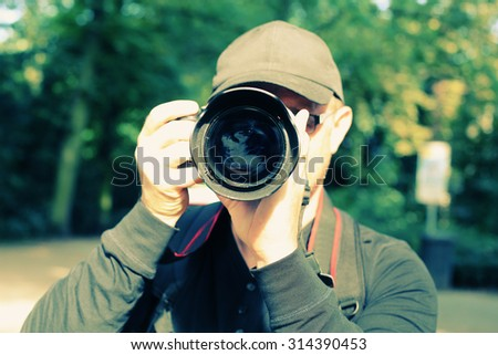 Young man with professional camera outdoors - stock photo