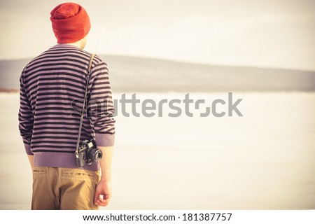 Young Man with retro photo camera outdoor hipster Lifestyle with mountains winter nature on background - stock photo