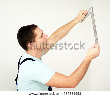 Young man with ruler. Room repair - stock photo